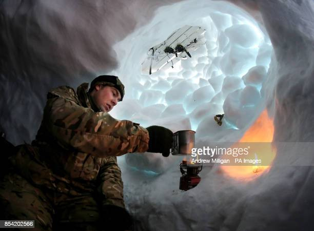 Marine Alistair McGoldrick from Chorley boils water from snow in his snow hole they built and camped in as troops take part in Exercise Hairspring...