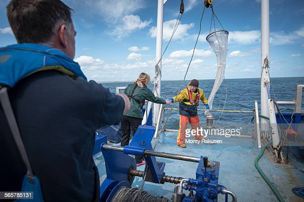 Marine biologists taking samples from plankton net on research ship