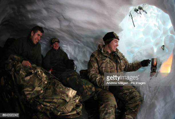 Marine Callum Kelly from Manchester Marine Craig Connor from Liverpool and Marine Alistair McGoldrick from Chorley boil water from snow in their snow...