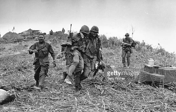Marine carrying a wounded colleague down Hill Timothy during the Vietnam War