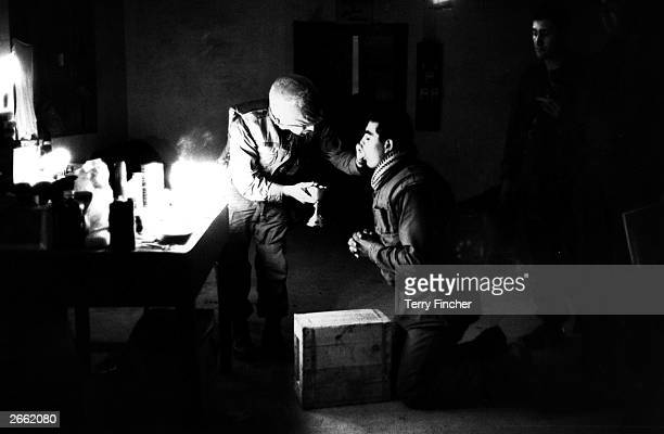 Marine chaplain Eli Tavesian giving communion to marine Louis A Loya at Forward Command Post in Hue Vietnam
