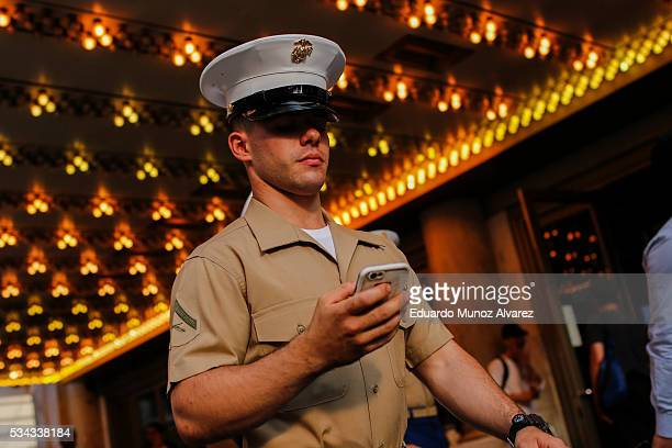 A marine checks his mobile phone as he walks around Times Square during Fleet Week on May 25 2016 in New York City Nearly 4500 Sailors Marines and...