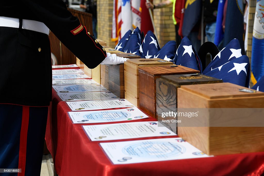 Marine Corp Sgt. Caleb Stowers places his hand on the urn of a cremated remains of a Veteran at Ft. Logan Cemetery June 25, 2016. Missing in America Project interned the unclaimed remains of 30 WWII, Korea, and Vietnam Veterans at the Ft. Logan National Cemetery of June 25, 2016.
