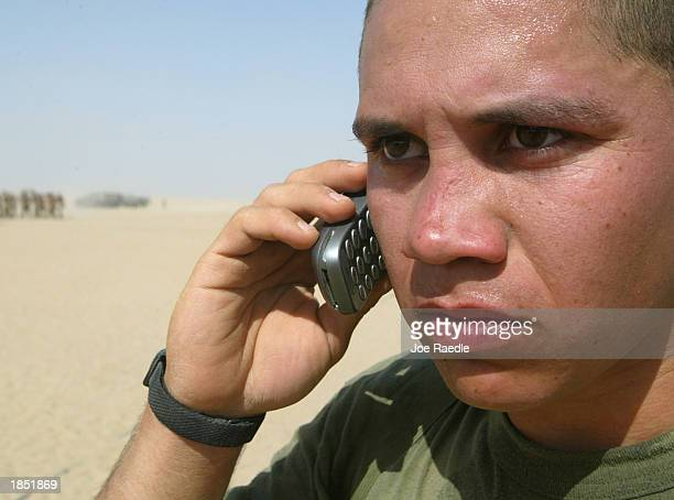 S Marine Corporal Juan Lopez of Task Force Tarawa gets to make a telephone call home after winning a running competition March 16 2003 at Camp Shoup...