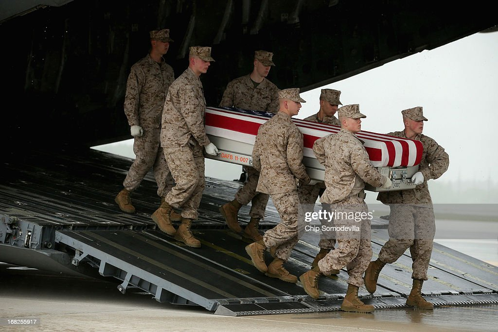 S. Marine Corps carry team carries the flag-draped transfer case with the remains of Marine Staff Sgt. Eric Christian of Warwick, New York off of a C-17 on the tarmac at Dover Air Force Base May 7, 2013 in Dover, Delaware. Assigned to 2nd Marine Special Operations Battalion out of Camp Lejeune, North Carolina, Christian and one other Marine died May 4, while conducting combat operations in Farah province, Afghanistan.