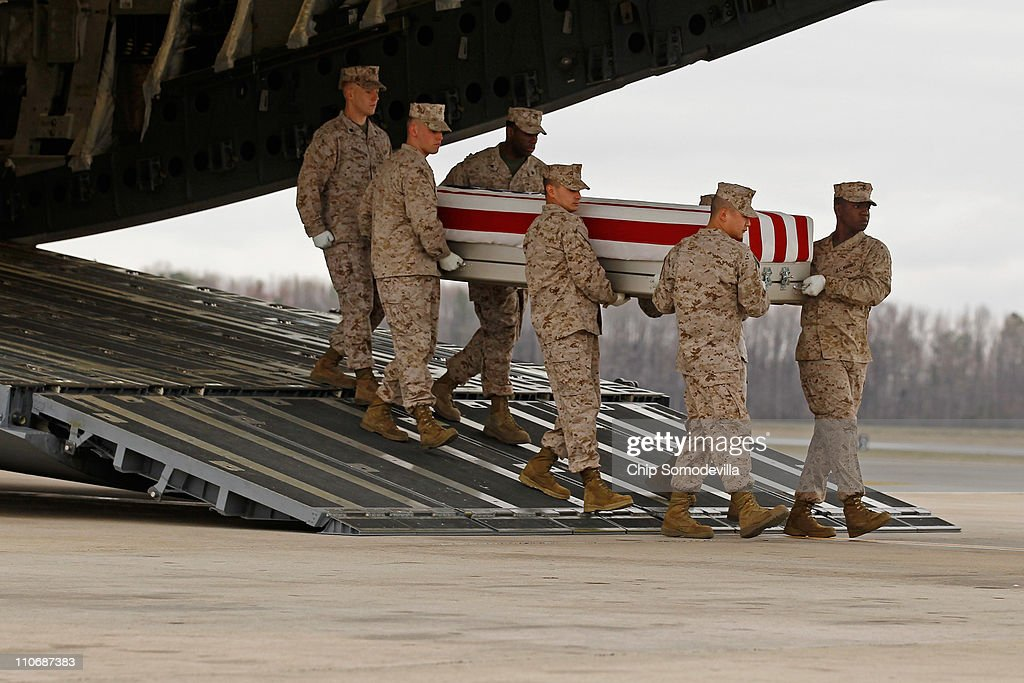 S. Marine Corps carry team moves the flag-draped transfer case with the remains of Marine Staff Sgt. James Malachowski off an Air Force C-17 tranport plane on the tarmac at Dover Air Force Base March 23, 2011 in Dover, Deleware. A platoon sergeant with the 3rd Platoon, Fox Company, 2nd Battalion, 8th Marine Regiment, 2nd Marine Division, II Marine Expeditionary Force, Malachowski of Westminster, Maryland, was on his fourth combat deployment when he was killed in action March 20 in Afghanistan.