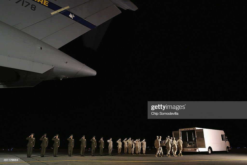 S. Marine Corps carry team transfers the remains of Lance Cpl. Brandon Garabrant of Peterborough, New Hampshire, from an C-17 aircraft to a transfer vehicle as senior ranking officers, including Commandant of the Marine Corps Gen. James Amos (L), salute at Dover Air Force Base June 23, 2014 in Dover, Delaware. Members of the 2nd Combat Engineer Battalion, 2nd Marine Division, II Marine Expeditionary Force at Camp Lejeune, Garabrant, Staff Sgt. David Stewart of Stafford, Virginia; and Lance Cpl. Adam Wolff of Cedar Rapids, Iowa were killed Friday when their vehicle was struck by a roadside bomb in Helmand province in southern Afghanistan.