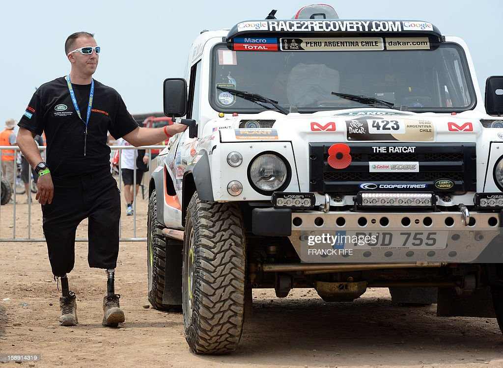 US Marine Corps former minesweeper Mark Zambon, member of the team Race 2 Recovery, consisting of British and US soldiers who have suffered serious injuries in the conflicts in Iraq and Afghanistan in recent years, stands next to a car in Lima on January 3, 2013, ahead of the 2013 Dakar Rally which this year will thunder through Peru, Argentina and Chile from January 5 to 20. AFP PHOTO / FRANCK FIFE