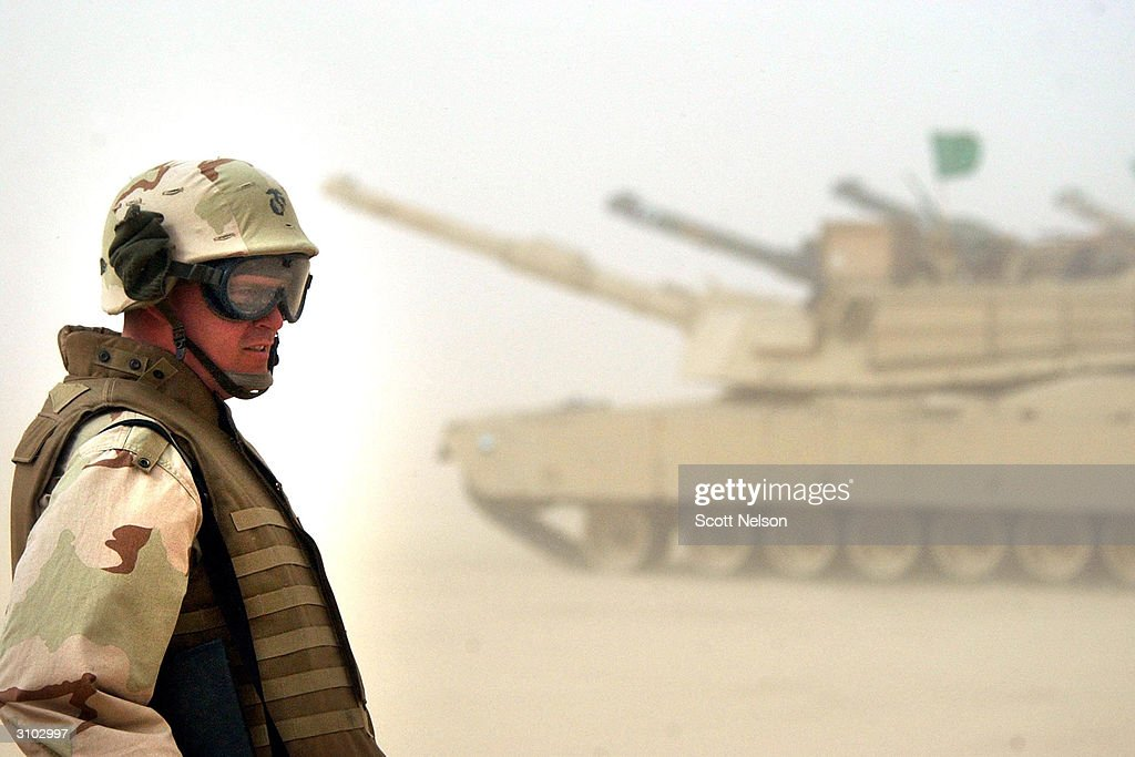 S Marine Corps Lance Corporal Brent Walker from Harrisburg Illinois watches a group of M1/A1 Abrahms tanks prepare for exercises February 3 2003 near...