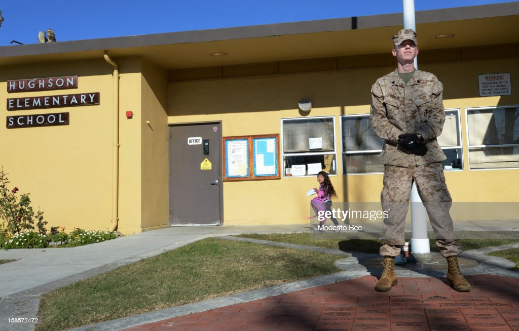 U.S. Marine Corps Reserve Sgt. Craig Pusley stands guard as kindergarten student Liset Corona, 5, walks to her class at Hughson Elementary School on Wednesday, December 19, 2012, in Modesto, California. 'I swore to defend this country from all enemies, foreign and domestic,' Pusley said after volunteering to stand watch. Asked about his lack of firepower, Pusley said, 'I don't need to be armed to do this.'