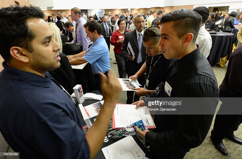 U.S. Marine Corps veteran from Iraq and Afghanistan wars, Nicholas Herandez (L), listens to a representative from Raytheon Company during a jobs fair for veterans called 'Serving Those Who Have Served' on campus on March 20, 2013 in Los Angeles, California. California's unemployment rate tied with Rhode Island's for highest in U.S. at 9.8 percent.
