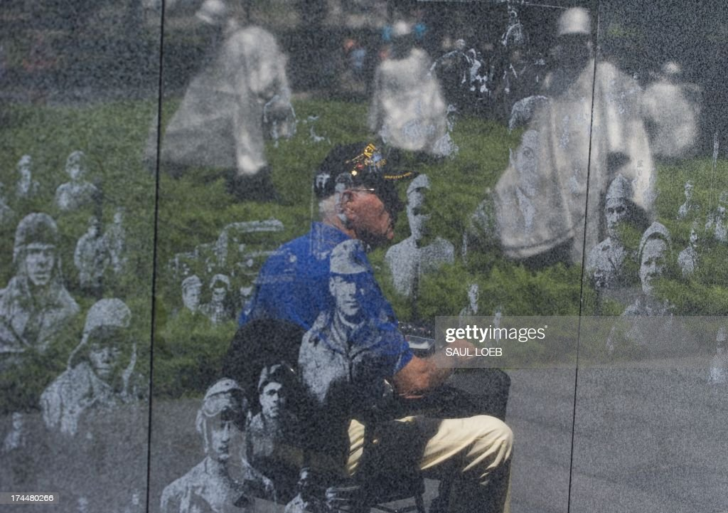 US Marine Corps Veteran Tommie Mabe of Daytona Beach, Florida, who fought in the Korean War, is reflected in the Korean War Veteran Memorial on the National Mall in Washington, DC, July 26, 2013. July 27 marks the 60th anniversary of the Korean War Armistice agreement and will be marked by a special ceremony in Washington with a speech by US President Barack Obama. AFP PHOTO / Saul LOEB