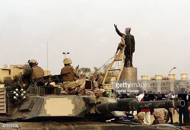 A US marine covers the face of a statue of Iraqi dictator Saddam Hussein with an American flag on April 9 2003 at alFardous square in Baghdad Iraq...