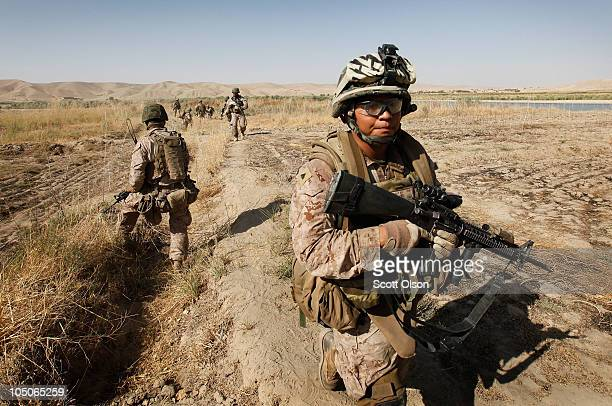 S Marine Cpl Marcus Chischilly of Phoenix AZ attached to India Batery 3rd Battalion 12th Marine Regiment patrols near Forward Operating Base...