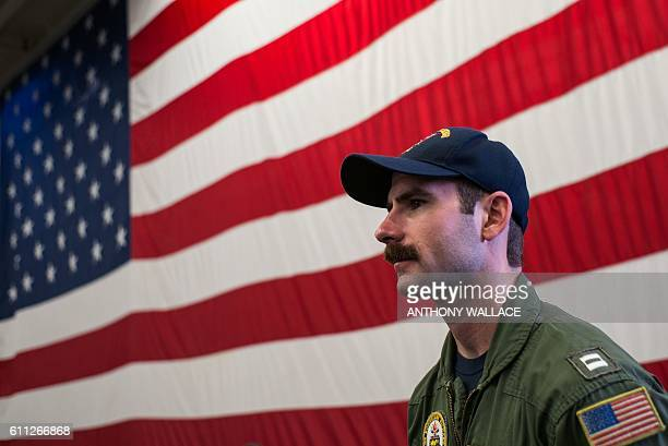 Marine crew member stands in front of the US flag on the USS Bonhomme Richard during a port call in waters off Hong Kong on September 29 after its...