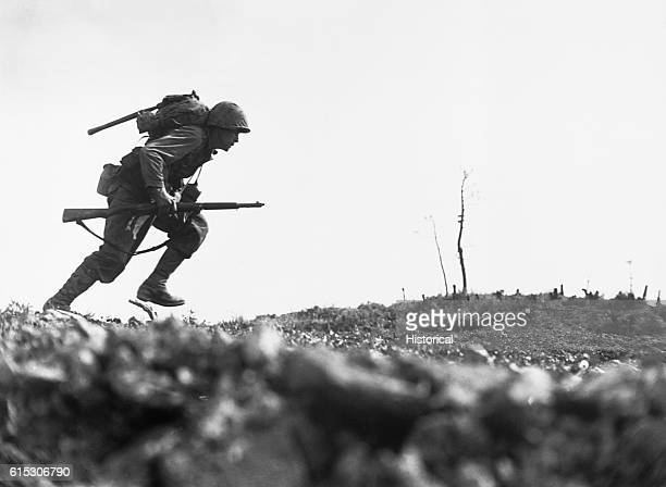 A U S Marine dashes through Japanese machine gun fire while crossing a draw called Death Valley by the men fighting there Marines sustained more than...