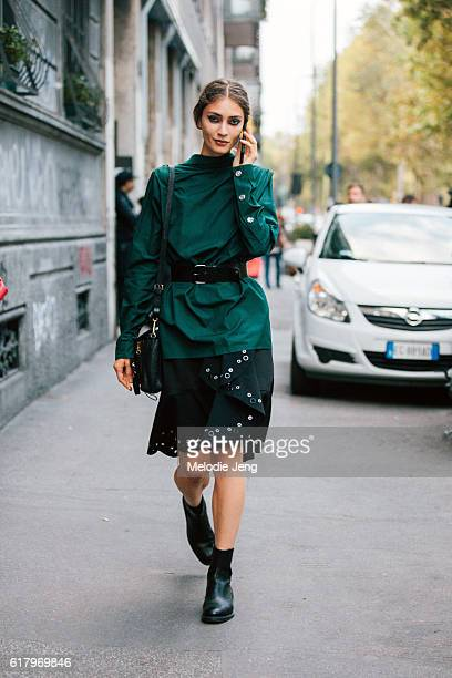 Marine Deleeuw wears a belted green N21 shirts backwards over a Proenza Schouler grommet skirt while on the phone after the N21 show during Milan...