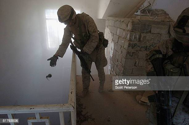Marine drops a grenade down a stairwell to clear a lower floor as US Marines of the 1st Light Armored Reconnaissance company as part of 1st Battalion...