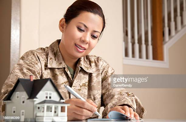US Marine Female Soldier at Home with Real Estate Paperwork