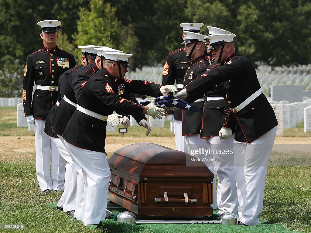 Marine folds an American flag over the remains of US Marine PFC Anthony Brozyna of Hartford CT during a full honor burial service at Arlington...
