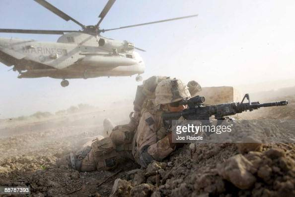 S Marine from 2nd Marine Expeditionary Brigade RCT 2nd Battalion 8th Marines Echo Co takes up a fighting position after off loading from a helicopter...