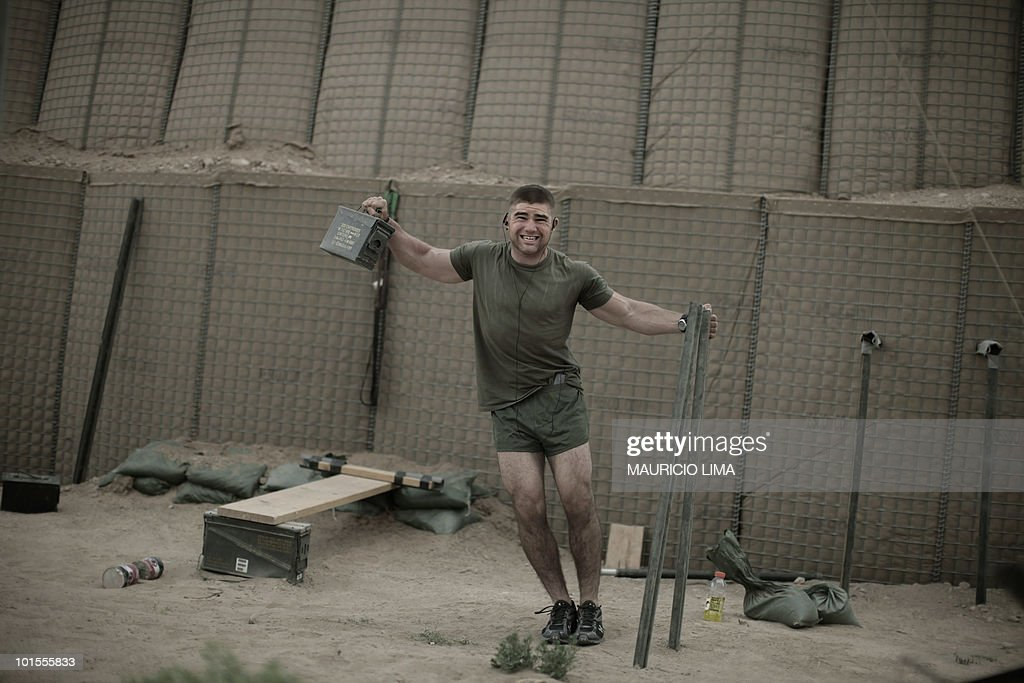 Marine from India Company, 3rd Battalion, 6th Marines, performs exercises at an outdoor improvised gym at nightfall, at a combat outpost in Marjah, Helmand province, southern Afghanistan, on April 11, 2010. Most US Marines involved in the operations against the Taliban in Marjah still have no laundry service and have not taken a proper shower since end of January. However, the place where they will spend more than a week, US Marines built an improvised outdoor gym using only raw materials they could find around them like wooden pole, pull-up bars, dip station, ammunition cases, truck chain and filled up sandbags. AFP PHOTO/Mauricio LIMA