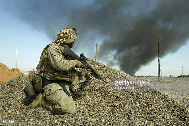 Marine from the 1st Marine Division deploys in the town of alNasr Wa alSalam near Fallujah 28 March 2004 Two days after battling insurgents in this...