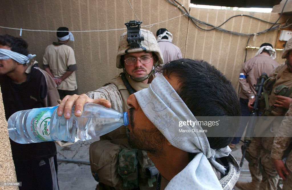 S. Marine from the 1st U.S. Marines Expeditionary Force, 1st Battalion, 3rd Marines Regiment, Bravo Company, gives some drinking water to an arrested Iraqi man November 13, 2004 in Fallujah, Iraq. According to Iraqi National Security Adviser Kasim Dawood, 1000 insurgents have been killed and 200 insurgents have been captured during the six-day battle. U.S. Marines have been arresting males between the combat age of 15 and 55-years-old.