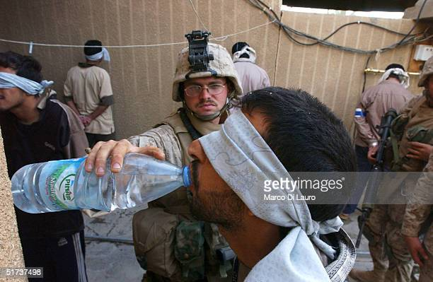 S Marine from the 1st US Marines Expeditionary Force 1st Battalion 3rd Marines Regiment Bravo Company gives some drinking water to an arrested Iraqi...