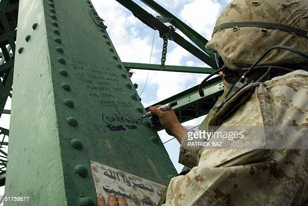 US marine from the 3/5 Lima company writes a message under graffiti scribbled on the bridge crossing the Euphrates River in the restive city of...