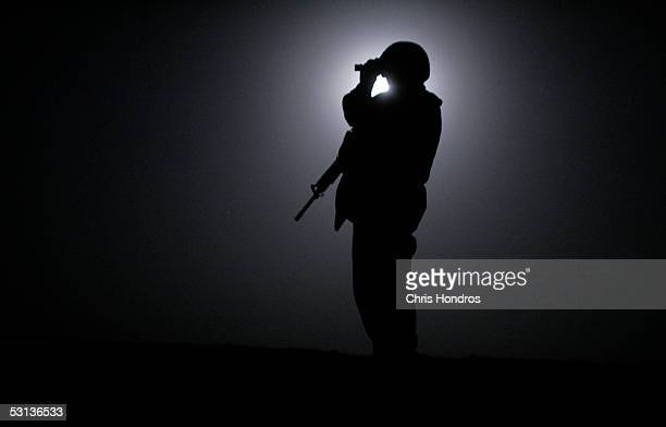 Marine from the 3rd Battalion Fourth Marines scans the horizon with night vision goggles while silouetted by the moon during midnight patrol around...