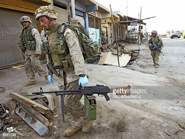US marine from the First Battalion Fifth Marines carry a Russian made RPK heavy machinegun taken from Sunni Muslim insurgents near the industrial...
