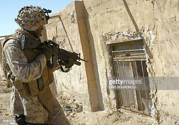 US marine from the First Battalion Fifth Marines watches a window in an industrial area of Fallujah 50 km West of Baghdad as he protects a Civil...