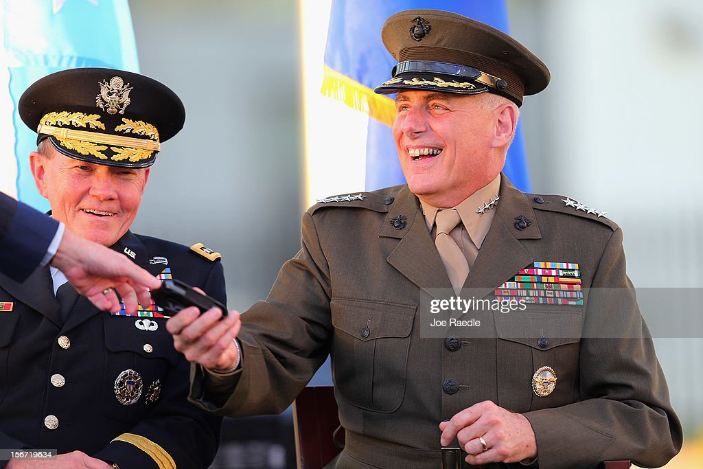 U.S. Marine General John F. Kelly (R) shares a laugh with U.S Army General Martin E. Dempsey, Chairman, Joint Chiefs of Staff, as he is handed a Blackberry phone by U.S. Air Force General Douglas Fraser during a change of command ceremony at United States Southern Command on November 19, 2012 in Doral, Florida. U.S. Marine Gen. John Kelly takes over the command from U.S. Air Force Gen. Douglas Fraser.