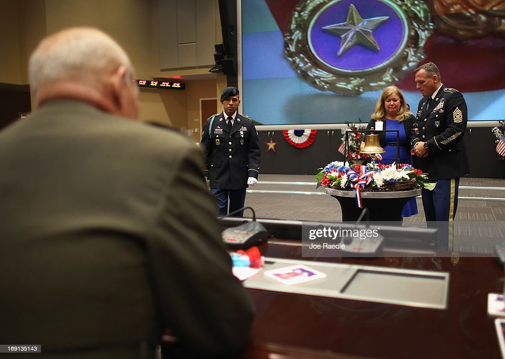 U.S. Marine General John Kelly (L back to camera) watches as his wife, Karen Kelly, escorted by U.S. Army Command Sergeant Major William B. Zaiser prepares to ring a bell in honor of their son, U.S. Marine Lieutenant Robert Kelly, during a ceremony to remember and honor those who have died in service to the nation and the families they have left behind at U.S. Southern Command headquarters on May 20, 2013 in Doral, Florida. U.S. Marine Gen. John Kelly presided over the ceremony where the families of 57 fallen service members from South Florida were invited to attend.