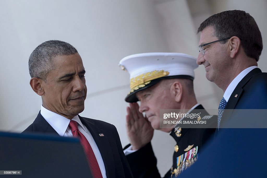 Marine General Joseph Dunford (C), Chairman of the Joint Chiefs of Staff, and US Secretary of Defense Ashton Carter (R) wait as US President Barack Obama arrives during an event to honor Memorial Day at Arlington National Cemetery May 30, 2016 in Arlington, Virginia. / AFP / Brendan Smialowski
