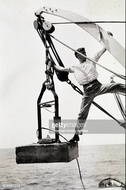 Marine geologist on a survey planting a hydrophone anchor with the cable attached The Hydrophone would pick up sound from an underwater man made...