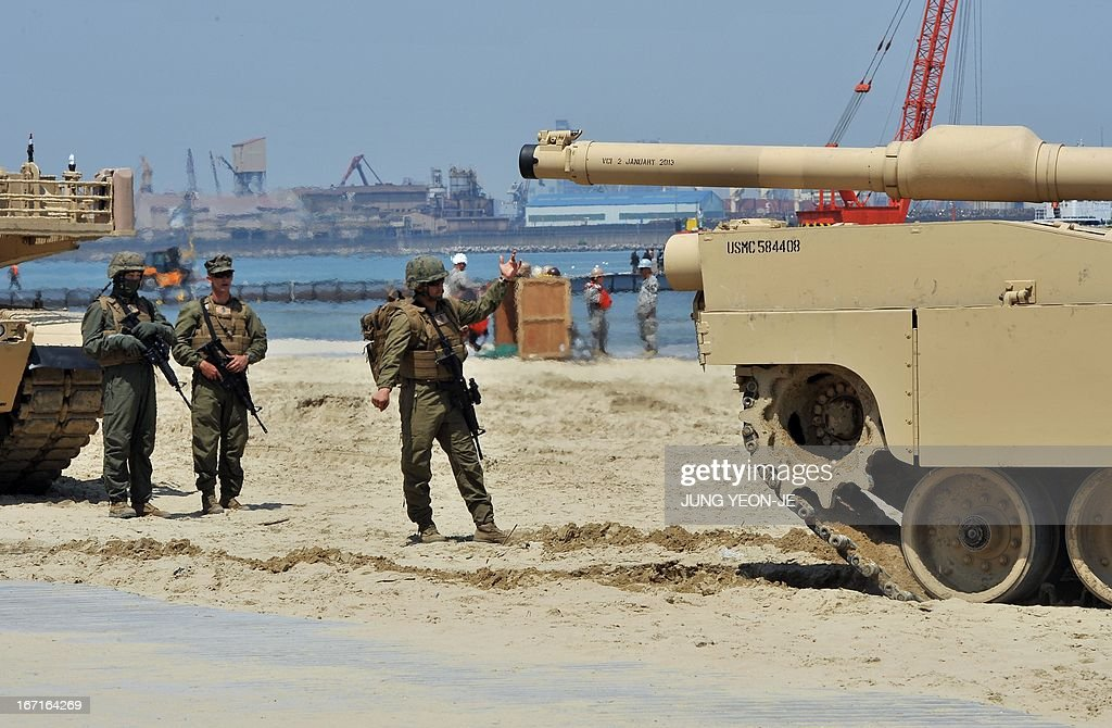 Marine (C) gestures to an M1A1 tank (R) at a beach during the Combined Joint Logistics Over the Shore (CJLOTS) exercise in Pohang, 260 kms southeast of Seoul, on April 22, 2013. The wait for North Korea's expected missile test, which has kept South Korean and US forces on heightened alert for the past two weeks, may stretch to July, the South's defence ministry said on April 22.