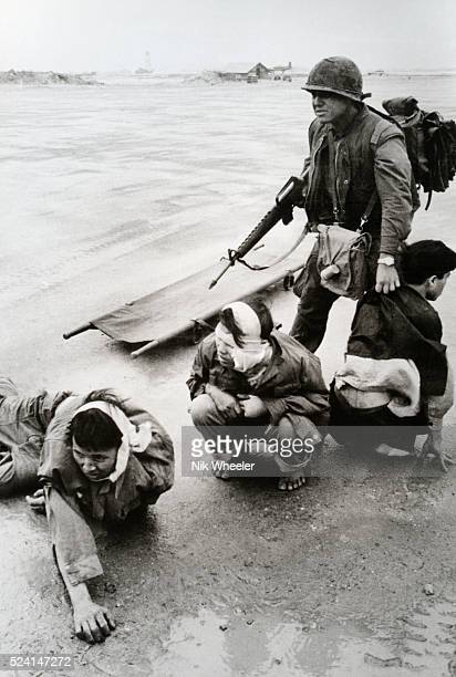 US Marine guards three NVA prisoners on Phu Bai airstrip South Vietnam The prisoners had been captured during fighting in the city of Hue which the...