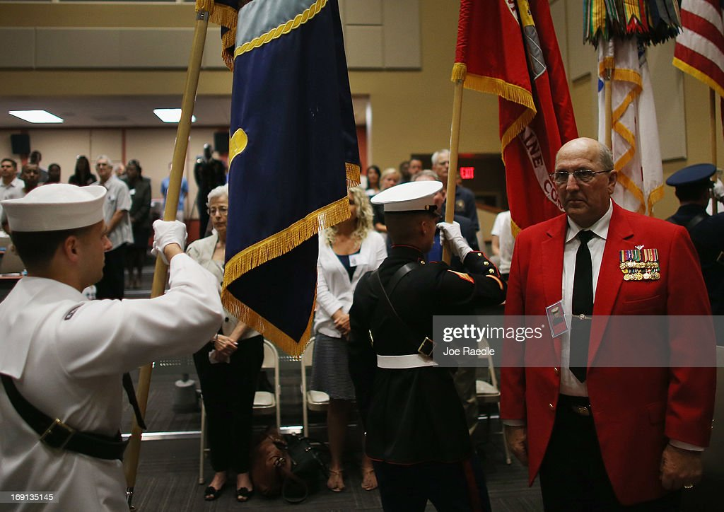 U.S. Marine Gunnery Sergeant Louis Slagle (R) stands as a military honor guard walks past during a ceremony to remember and honor those who have died in service to the nation and the families they have left behind at U.S. Southern Command headquarters on May 20, 2013 in Doral, Florida. U.S. Marine Gen. John Kelly presided over the ceremony where the families of 57 fallen service members from South Florida were invited to attend.