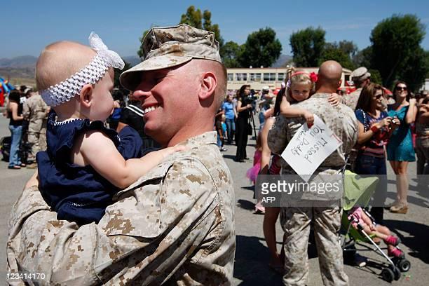 Marine Gunnery Sgt Christopher Krivenko holds his ninemonthold daughter Bree while Marine Capt Stephen Kulas holds his threeyearold daughter Zoe as...