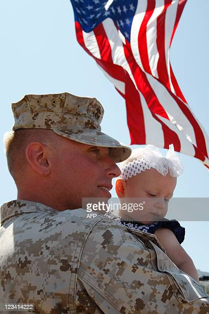 Marine Gunnery Sgt Christopher Krivenko holds his ninemonthold daughter Bree as approximately 270 US Marines and sailors with Regimental Combat Team...