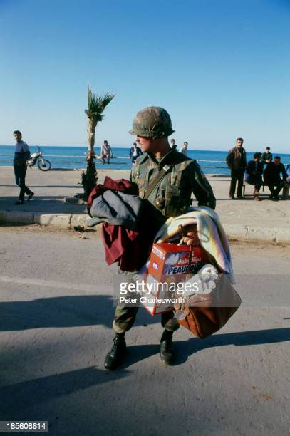 Marine helps in the evactuation of American European and other foreign civilians who are being ferried by US military helicopters to ships off the...