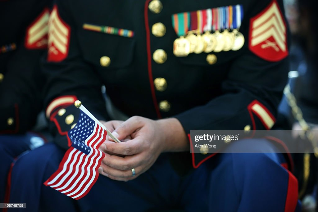 S Marine holds a US flag during a naturalization ceremony November 10 2014 at the National Museum of the Marine Corps in Triangle Virginia Service...