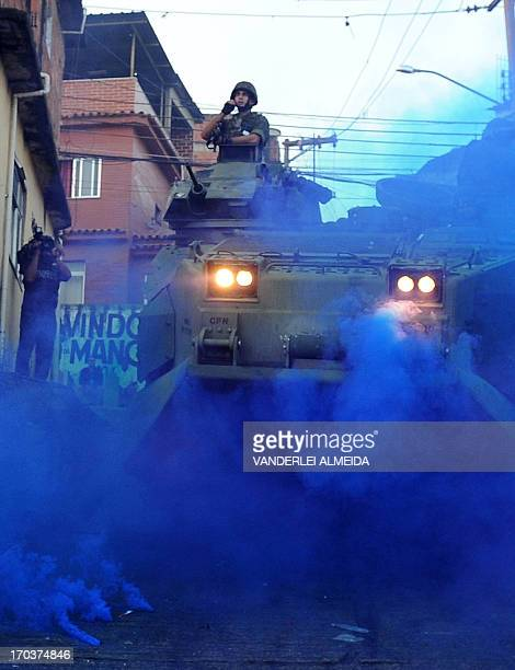 A marine in an armored personnel carrier throws a blue smoke flare in Rio de Janeiro's Morro da Mangueira shantytown as he advances through the...