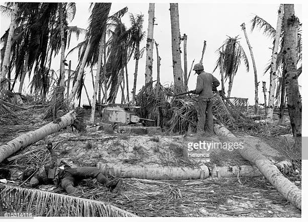 Marine inspects a reveted Japanese tank used as a pillbox In the foreground a dead Japanese soldier lies grotesquely frozen by rigor mortis in a...