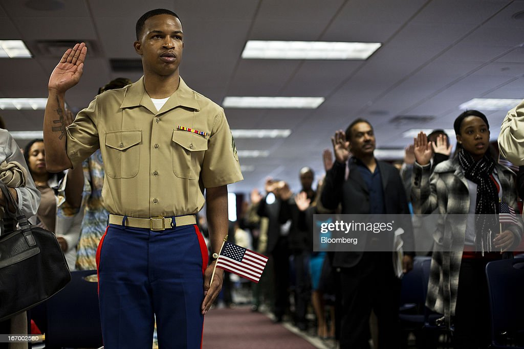 U.S. Marine Kenrick Cacho, left, and newly naturalized American citizens take the Oath of Allegiance during a Naturalization Ceremony at the Jacob K. Javits Federal Building in New York, U.S., on Friday, April 19, 2013. A Senate plan to rewrite U.S. immigration law has stoked a years-old debate over allowing undocumented residents a chance to become citizens, a measure viewed by opponents as rewarding lawbreakers with 'amnesty' and undercutting American workers. Photographer: Victor J. Blue/Bloomberg via Getty Images