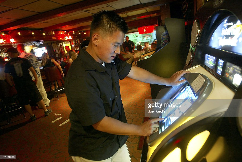Marine Lance Corporal Jonathan Chang from 1/2 Charlie Company of Task Force Tarawa picks songs to play from a jukebox after returning from deployment...