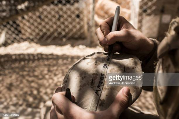 S marine Lance Corporal Michael McLeod writes vital information on his helmet at Camp Bost on September 11 2017 in Helmand Province Afghanistan About...