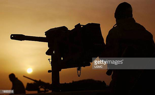 S Marine Lance Cpl Raetheon Mitchell cleans his MK19 automatic grenade launcher at daybreak as convoy operations continue April 12 2003 at the...